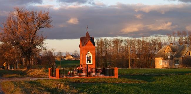 Kapliczka  położona na ternie wsi Piekuty Urbany, w tle wieś Łopienie Jeże